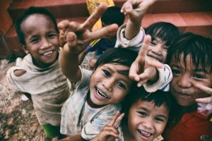 young Vietnamese children smiling and making peace signs